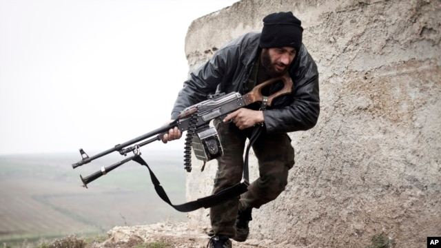 FILE - Free Syrian Army fighter takes cover during fighting in Azaz.