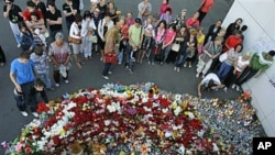 People place candles, toys and flowers as they observe a day of mourning for victims of a cruise vessel that sank July 10 at the port of Kazan, Russia, July 12, 2011 (file photo) (AP Photo/Misha Japaridze)