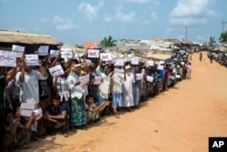 FILE - Rohingya refugees holding placards await the arrival of a U.N. Security Council team at the Kutupalong Rohingya refugee camp in Kutupalong, Bangladesh, April 29, 2018.