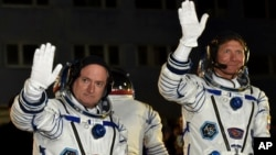 FILE - Russian cosmonaut Gennady Padalka, right, and U.S. astronaut Scott Kelly, crew members of the mission to the International Space Station, ISS, wave prior to the launch of Soyuz-FG rocket at the Russian-leased Baikonur cosmodrome, Kazakhstan, March 27, 2015.