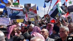 In a photo released by Syrian official news agency SANA, Syrians hold national flags and portraits of Syrian President Bashar Assad during a protest against President Donald Trump's move to recognize Israeli sovereignty over the occupied Golan Heights, in Homs, March 26, 2019.