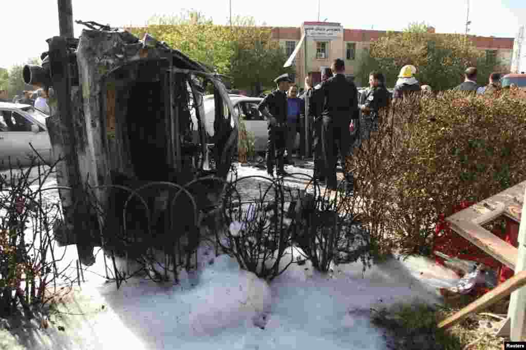 Pasukan keamanan Kurdi berdiri di samping bangkai mobil yang dipakai untuk serangan di Irbil (19/11).(Reuters/Azad Lashkari)
