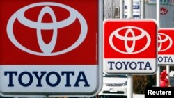 FILE - Toyota Motor signboards are displayed at a dealer's shop in Yokohama, south of Tokyo. The recall involves Toyota's popular RAV4 and RAV4 electric models produced between 2005 and 2014.