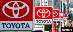 FILE - Toyota Motor Corp. signboards are displayed at a dealer's shop in Yokohama, south of Tokyo.