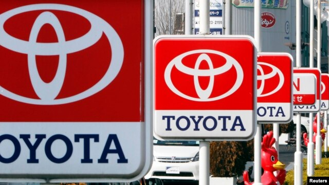 FILE - Toyota Motor signboards are displayed at a dealer's shop in Yokohama, south of Tokyo.