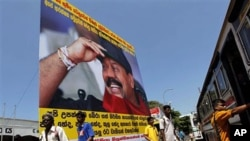 Sri Lankans walk past a billboard of President Mahinda Rajapaksa and campaign slogans for people to join the protest against the U.N. report, Colombo, Apr 21 2011