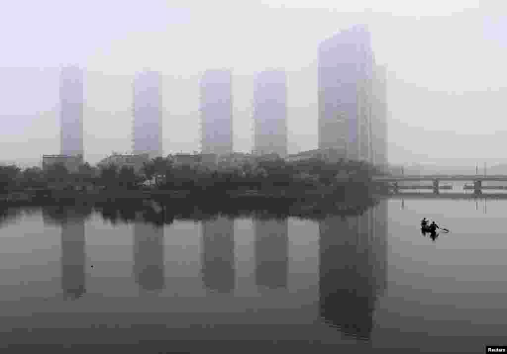 Một người đàn ông chèo thuyền trên sông trong một buổi sáng đầy sương mù ở Thiệu Hưng, tỉnh Chiết Giang, 16 tháng 6 năm 2013.