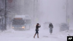 A woman shields her face from the wind-driven snow while making her way through a winter storm in downtown Portland, Maine, Feb. 2, 2015.