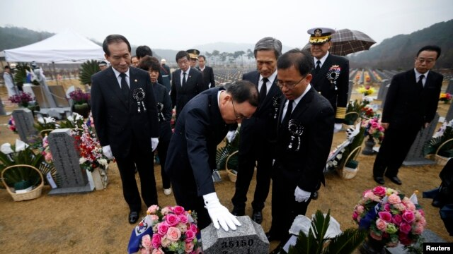 South Korean Prime Minister Jung Hong-won, center, pays respects at the grave of a sailor killed in the 2010 sinking of the Cheonan at National Cemetery, Daejeon, March 26, 2014.