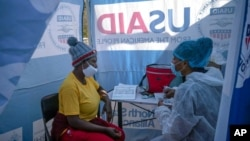 FILE - Nurse Nomautanda Siduna talks to a patient who is HIV-positive inside a gazebo used as a mobile clinic in Ngodwana, South Africa, July 2, 2020.
