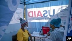 ພະຍາບານ ໂນມາວທານດາ ຊີດູນາ ລົມກັບຄົນໄຂ້ ຜູ້ທີ່ຖືກກວດເປັນຜົນບວກສຳລັບເຊື້ອ HIV ຢູ່ໃນຕູບຜ້າ ທີ່ຖືກໃຊ້ເປັນໂຮງໝໍເຄື່ອນທີ່, ເມືອງ ເອັນກອດວານາ, ປະເທດ ອາຟຣິກາໃຕ້. 2 ກໍລະກົດ, 2020.