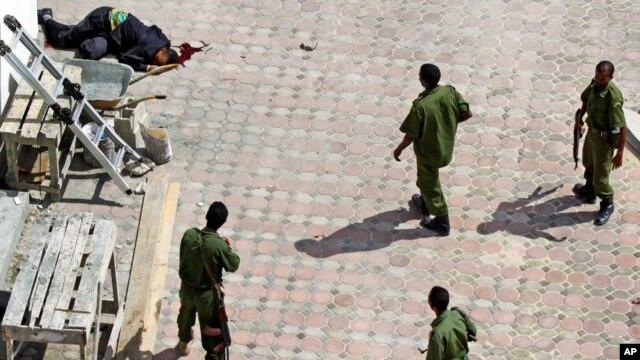 Sojojin Somaliya su na tsaye kusa da gawar wani da aka ce ma'aikacin hotel din ne a hagu, wanda ya mutu bayan tashin bama-bamai biyu a kusa da kofar shiga hotel din mai suna Jazeera Palace, hedkwatar wucin-gadi ta sabon shugaban Somaliya, Hassan Sheikh Mohamud.