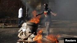 Un manifestant opposé au troisième mandat de President Pierre Nkurunziza fait un geste devant une barricade de flammes à Bujumbura, Burundi, jeudi 2015.