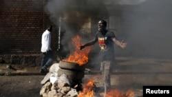 布隆迪首都布琼布巴街头一名抗议者站在燃烧的路障前(2015年5月14日)