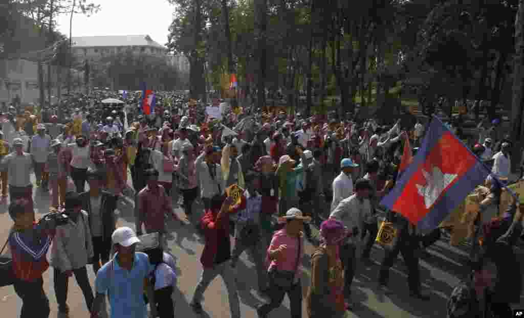 Para demonstran dipimpin oleh aktivis hak asasi manusia Mam Sonando berjalan melewati jalan utama meminta pemerintah mengijinkan pendirian saluran televisi baru di Phnom Penh, 27 Januari 2014.