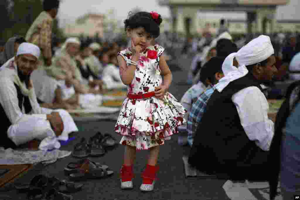 A Yemeni girl poses for a photograph as she attends the Eid al-Fitr prayer with her father, in Sanaa, Yemen, July 28, 2014.