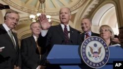 El vicepresidente Joe Biden (centro) junto al líder de la mayoría demócrata, Harry Reid (izq.) tras la votación en el Capitolio.