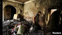A worker carries luggage from a house that burnt after an air strike by a Saudi-led coalition struck a nearby missile base, in Yemen's capital Sanaa, April 23, 2015.