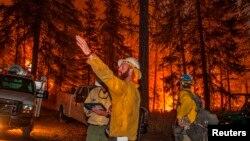 Petugas pemadam kebakaran bersiap menghadapi kebakaran hutan dekat Chelan, negara bagian Washington (16/8).