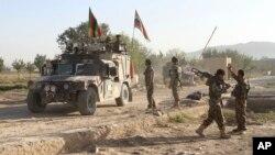 ທະຫານກອງທັບແຫ່ງຊາດ ອັຟການິສຖານ ຢືນປ້ອງກັນຢູ່ ໃກ້ໆສົບຂອງຜູ້ໂຈມຕີ ຕາລີບານ ຢູ່ຕໍ່ໜ້າຄຸກໃຫຍ່ ຫຼັງຈາກຈາກການຖືກໂຈມຕີ ໃນແຂວງ Ghazni, ພາກຕາເວັນອອກຂອງ ອັຟການິສຖານ, 14 ກັນຍາ, 2015.