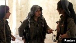 Di vê wêneya arşîvê de şervanên jin yên PKK'ê li Şengalê xwane dibin