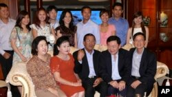 FILE PHOTO - Former Thai Prime Minister Thaksin Shinawatra, second right from the front row, and Cambodian Prime Minister Hun Sen, center, pose for photographs with other members of Hun Sen's family in his residence in Phnom Penh, Cambodia.