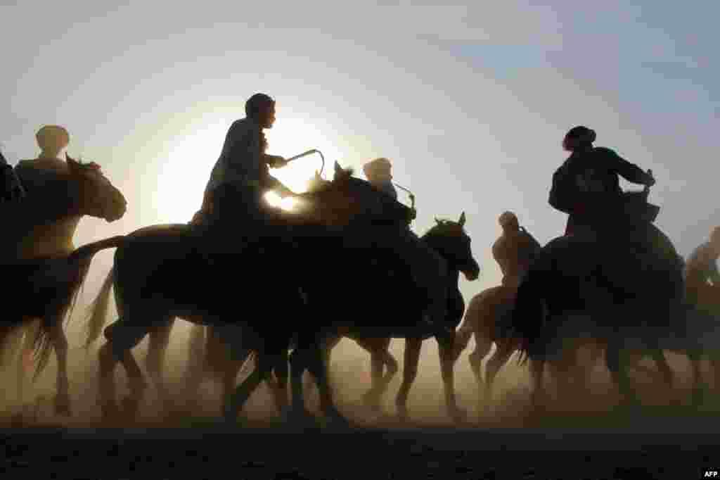 27 tháng 10: Các đấu thủ cỡi ngựa tham gia trò chơi Buzkashi ở Afghanistan. Hai toán cỡi ngựa thi đua bằng cách quăng những con bê, dê con và trừu con vào một vòng tròn để tính điểm. REUTERS/Omar Sobhani