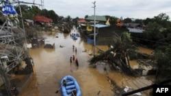 Nhân viên cứu hộ dùng thuyền cao su đi tìm người mất tích sau lũ quét tại thành phố Cagayan de Oro, Philippines, ngày 17 tháng 12, 2011