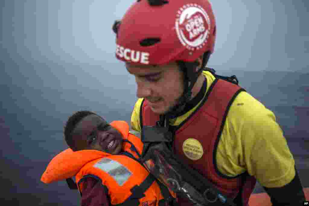 A member of Spanish NGO Pro activa Open Arms holds a baby rescued at a dinghy at Alboran Sea, about 40 miles (64 kms) from the Spanish coasts.