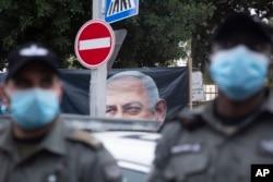 Polisi berjaga-jaga saat pengunjuk rasa anti-pemerintah Israel meneriakkan slogan di luar kediaman resmi Perdana Menteri Benjamin Netanyahu pada hari persidangan korupsi awalnya dijadwalkan sebelum ditunda, di Yerusalem, 13 Januari 2021.