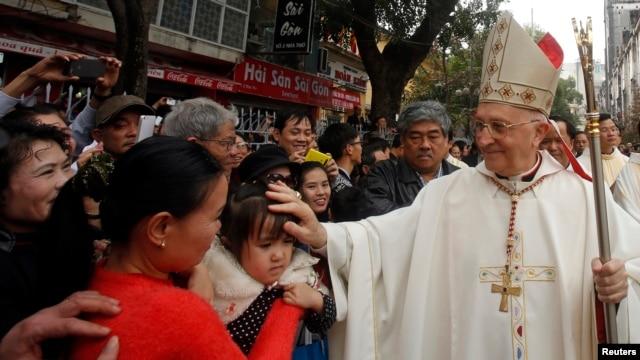 Đức Hồng Y Fernando Filoni (phải) ban phước cho một em bé trước Nhà thờ St. Joseph ở Hà Nội, ngày 20/1/2015.