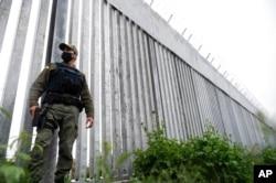 FILE - A policeman patrols alongside a steel wall at Evros River, near the village of Poros, at the Greek -Turkish border, Greece, May 21, 2021.