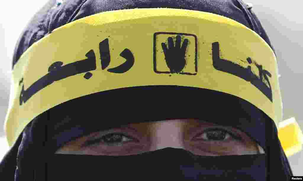 무슬림 형제단 소속 회원인 무르시 전 대통령의 지지자가 재판이 열리고 있는 군부 관할지역 앞에서 시위하고 있다.