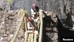 Members of the Huinchiri community rebuild an Incan hanging bridge, known as the Qeswachaka bridge, using traditional weaving techniques in Canas, Peru, June 13, 2021.