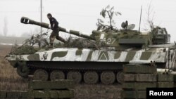 FILE - A member of the self-proclaimed Donetsk People's Republic forces walks atop a self-propelled artillery gun during tactical training exercises in Ukraine's Donetsk region, Feb. 4, 2016. Despite a peace deal, skirmishes between Kyiv forces and pro-Russia separatists continue in eastern Ukraine.