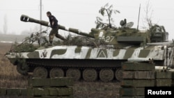 FILE - A member of the self-proclaimed Donetsk People's Republic forces walks atop a self-propelled artillery gun during tactical training exercises in Ukraine's Donetsk region, Feb. 4, 2016.