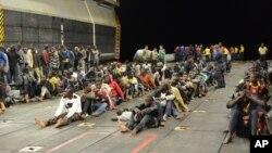 """救起的移民坐在美国海军两栖攻击舰""""巴丹号""""上"""