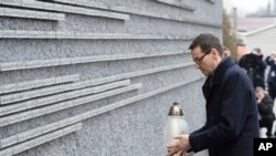 Polish Prime Minister Mateusz Morawiecki places a candle at a memorial wall with names of some of the Poles who saved Jews during the Holocaust, at the Ulma Family Museum of Poles Who Saved Jews during WWII, in Markowa, Poland, Feb. 2, 2018.