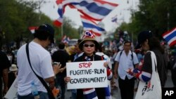"A protester holds a placard denouncing the government outside the government house in attempts to ""shutdown"" Bangkok, Thailand, Feb. 17, 2014."