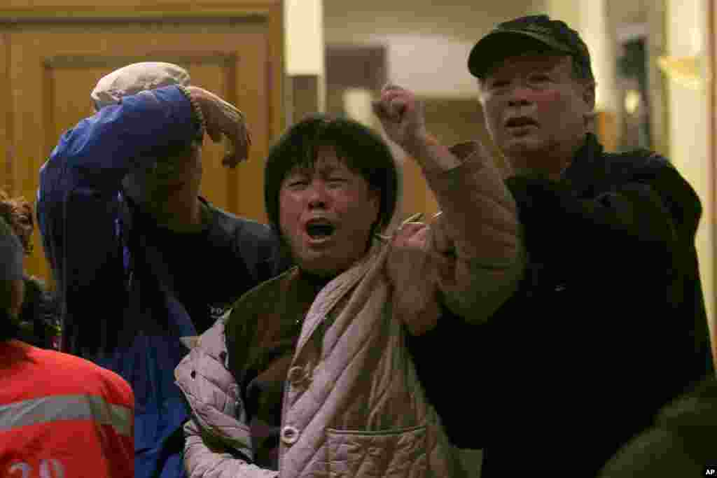 In Beijing, China, a relative of a Chinese passenger aboard Malaysia Airlines MH370 grieves after hearing that the missing plane is assumed to have crashed in the southern Indian ocean.