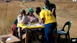 ANC party members check voters before they enter the polling stating in Mount Fletcher, Eastern Cape, South Africa, Wednesday, May 7, 2014. South Africa goes to the polls Wednesday in elections that are likely to see the ruling African National Congress. (AP Photo/Jerome Delay)