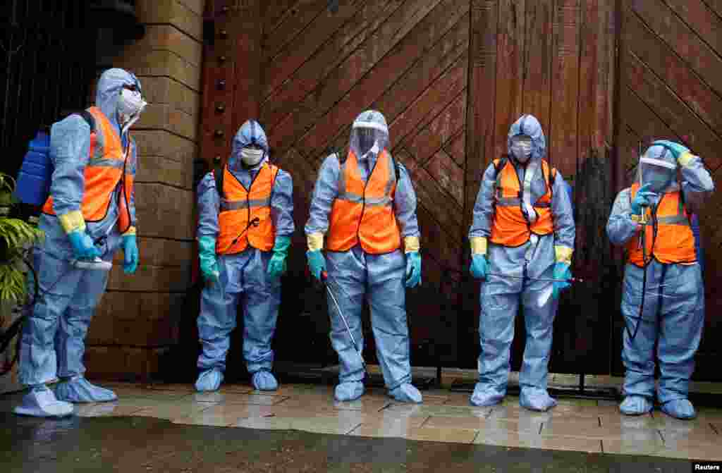 Municipal workers wearing personal protective equipment wait to enter Bollywood actor Amitabh Bachchan's residence for sanitization after he and his son, actor Abhishek Bachchan, tested positive for the coronavirus disease (CIVID-19), in Mumbai, India.