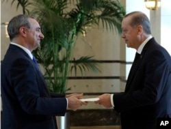 In this Dec. 5, 2016, photo, Turkey's President Recep Tayyip Erdogan, right, and the new Israeli Ambassador Eitan Naeh speak as Naeh presents his letter of credentials, in Ankara, Turkey.