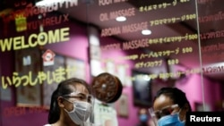 Therapists wearing face shields wait for costumers at a traditional Thai massage shop which reopened after the Thai government eased isolation measures to prevent the spread of the coronavirus disease (COVID-19) in Bangkok, Thailand, June 3, 2020. REUTERS