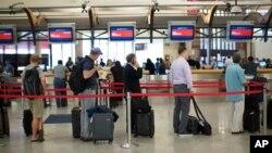 FILE - Passengers wait in line at Atlanta's Hartsfield International Airport in Atlanta.