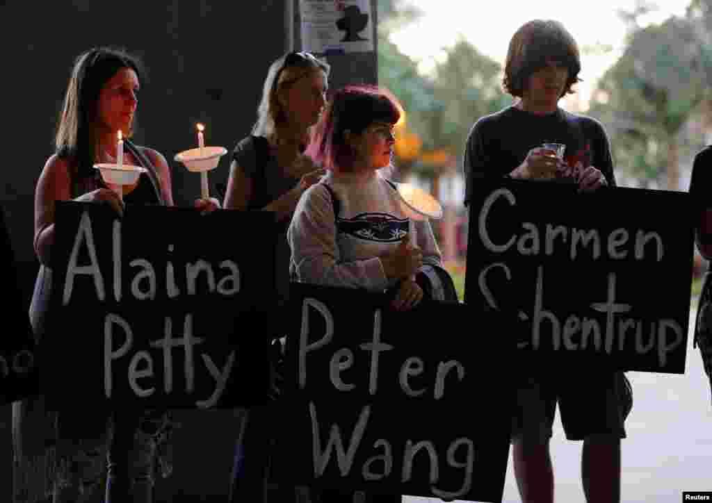 Para peserta memegang poster bertuliskan nama-nama korban di Parkland, Florida, dalam acara doa bersama di Florida Atlantic University, di Boca Raton, Florida, 16 Februari 2018.