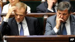 Polish Prime Minister Donald Tusk, left, and Deputy Prime Minister Janusz Piechocinski listen to lawmakers in the parliament in Warsaw, Poland, June 25, 2014.
