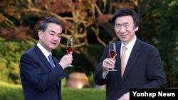 왕이 중국 외교부장(왼쪽)과 윤병세 한국 외교부 장관이 26일 서울 외교장관 공관에서 만찬을 갖기에 앞서 정원에서 건배를 하고 있다.