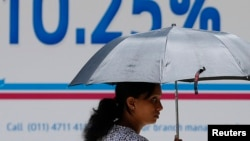FILE - A woman walks past an advertisement of a private bank in Colombo, Sri Lanka, Sept. 23, 2014.