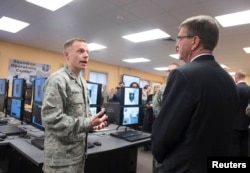 FILE - U.S. Defense Secretary Ashton Carter, right, is briefed on the capabilities of the National Guard Cyber Unit at Joint base Lewis-McChord, Washington, March 4, 2016.